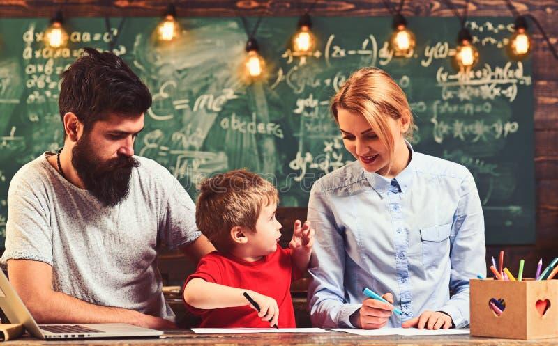Pittura della famiglia nelle penne del feltro su carta Il figlio con la madre ed il padre si siedono allo scrittorio Piccolo pitt fotografia stock