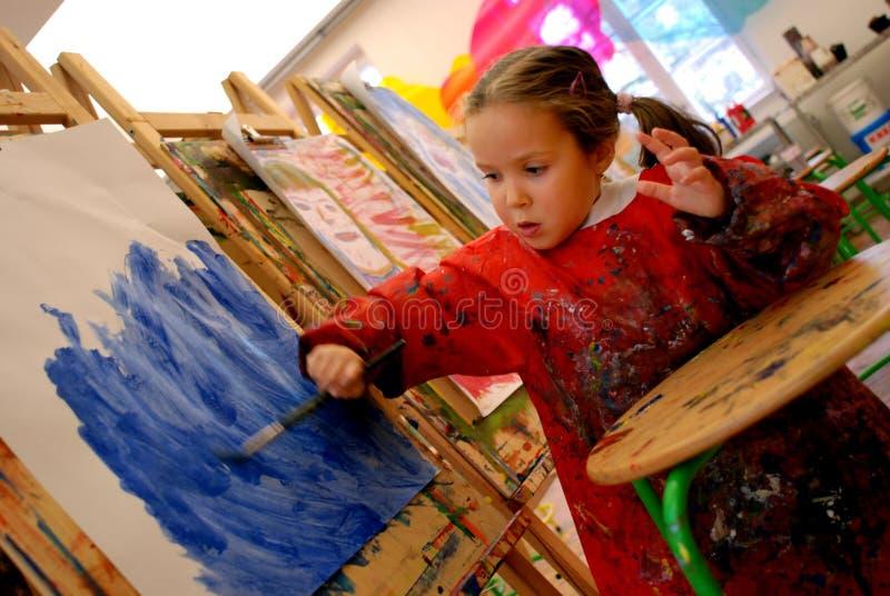 Pittura della ragazza con una spazzola fotografia stock