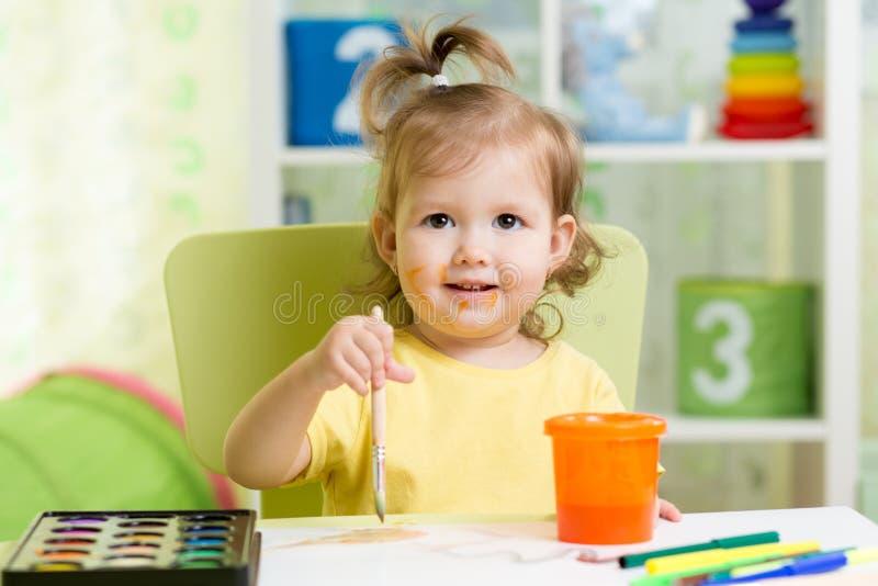 Pittura della ragazza del bambino con gli acquerelli a casa o la scuola materna prescolare immagine stock libera da diritti