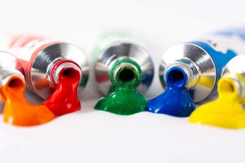 Pittura di gocciolamento del tubo di gouache e fondo bianco fotografia stock