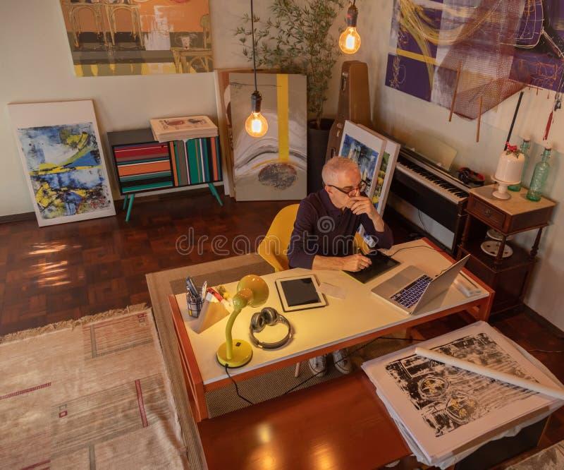 Pittura di mezza età dell'uomo dell'artista o disegnare digitalmente immagini stock libere da diritti