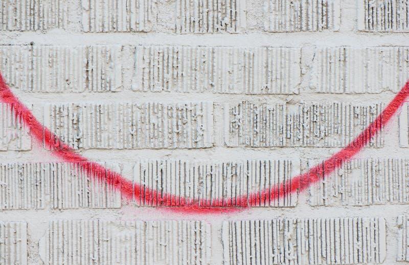 Pittura di spruzzo rossa sul muro di mattoni bianco immagine stock libera da diritti