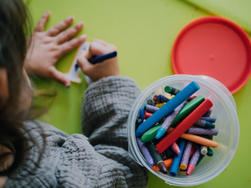 Pittura di tre anni della ragazza con i colori sulla tavola verde fotografia stock libera da diritti