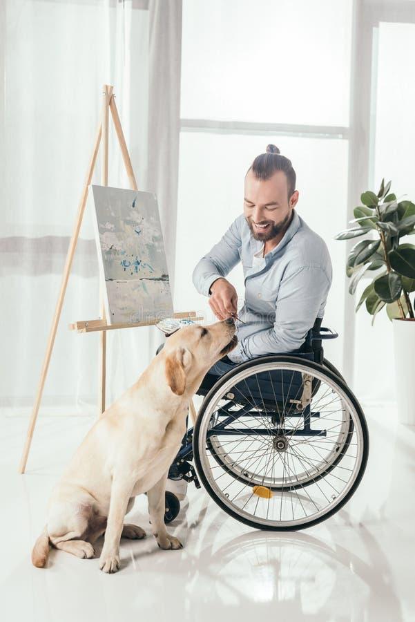 Pittura disabile dell'uomo e cane di coccole fotografia stock libera da diritti