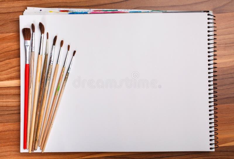 Pittura e libro di schizzo con le spazzole immagini stock