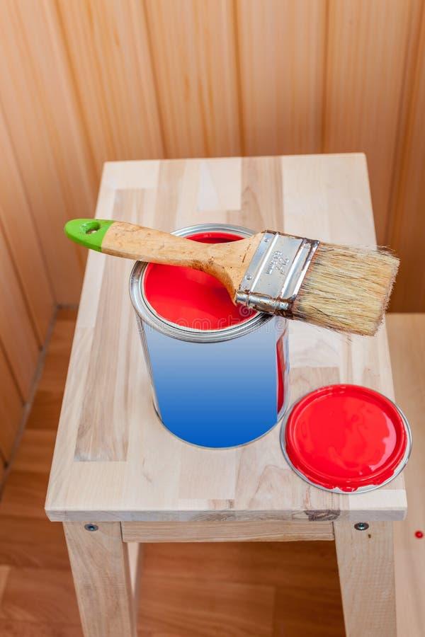 Pittura e spazzola rosse sulla sedia di legno immagini stock