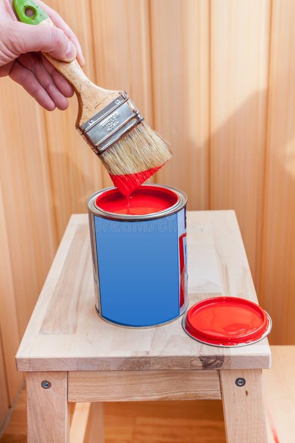 Pittura e spazzola rosse sulla sedia di legno fotografie stock