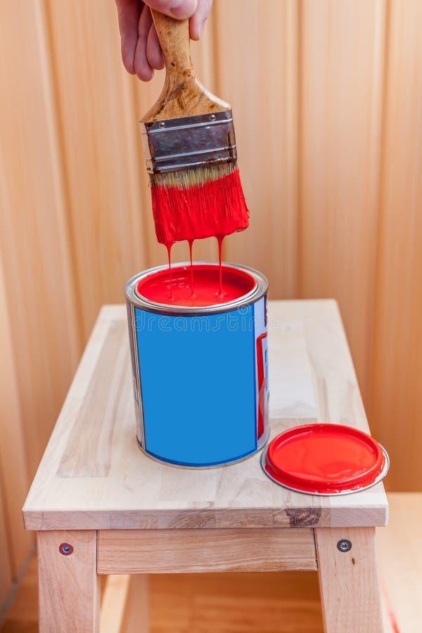 Pittura e spazzola rosse sulla sedia di legno fotografia stock