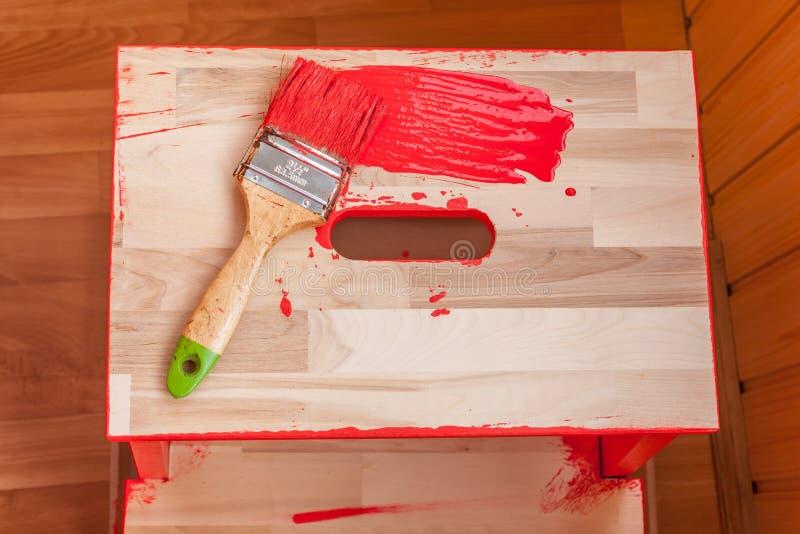 Pittura e spazzola rosse sulla sedia di legno immagine stock
