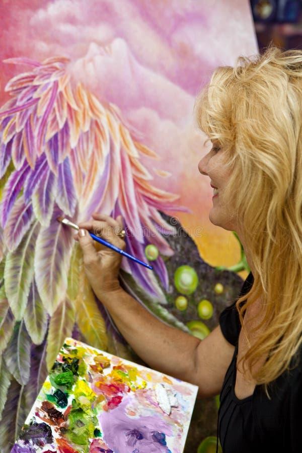 Pittura femminile dell'artista con l'olio su tela di canapa fotografie stock