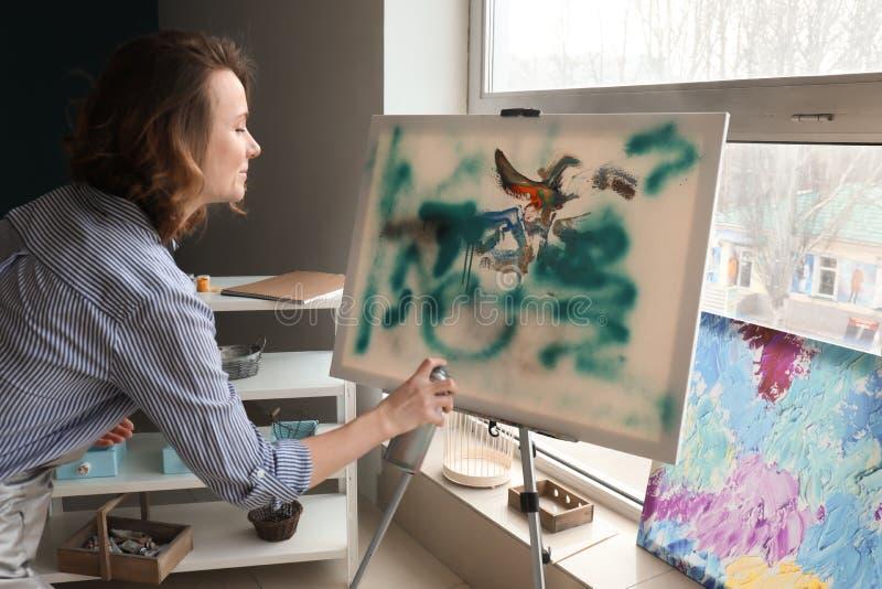Pittura femminile dell'artista con lo spruzzo di aerosol in officina immagini stock