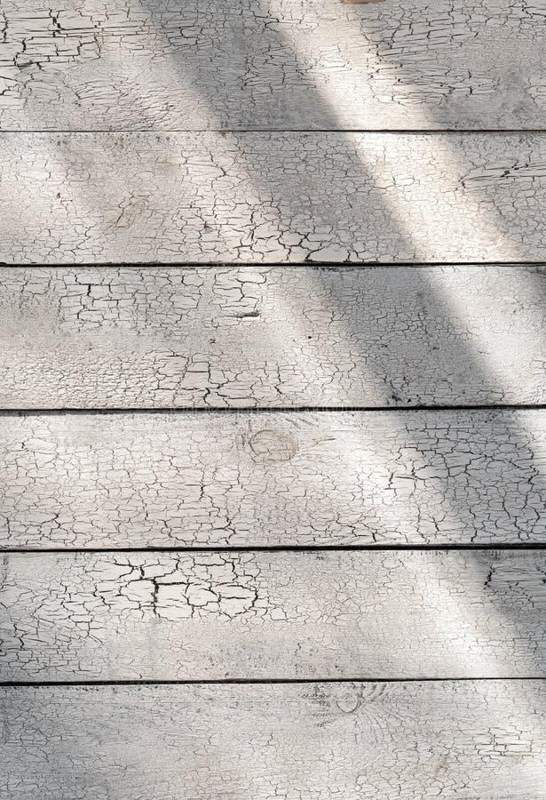 Pittura incrinata sulle plance rustiche misere del fondo di legno bianco con luce solare immagine stock libera da diritti