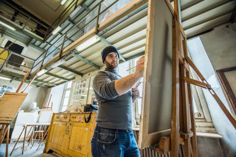 Pittura insegnante/dell'artista su una tela con un treppiede di legno immagine stock