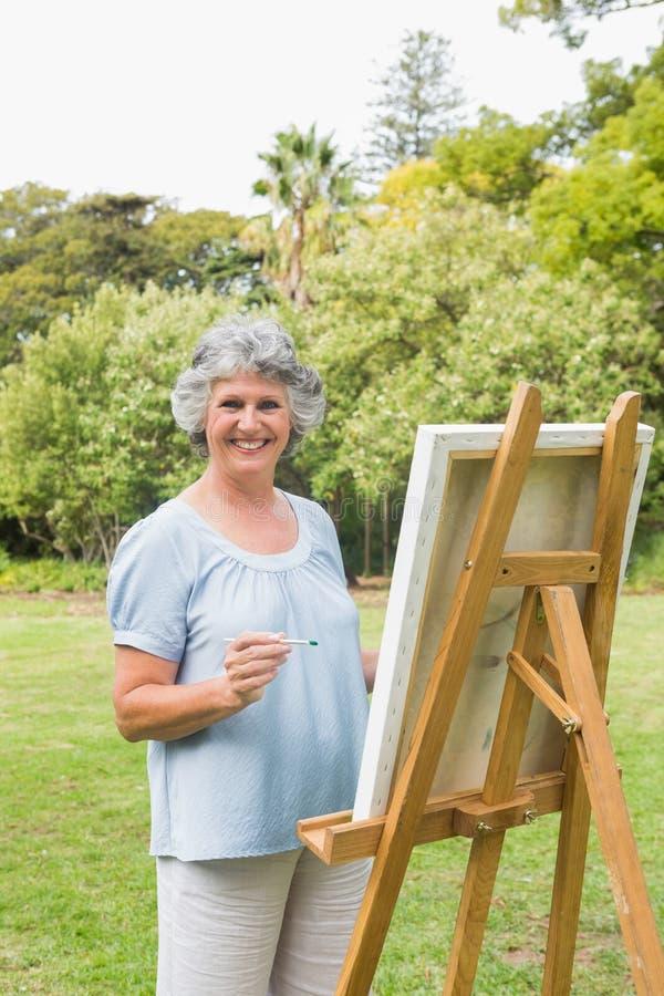 Pittura pensionata allegra della donna sulla tela immagini stock