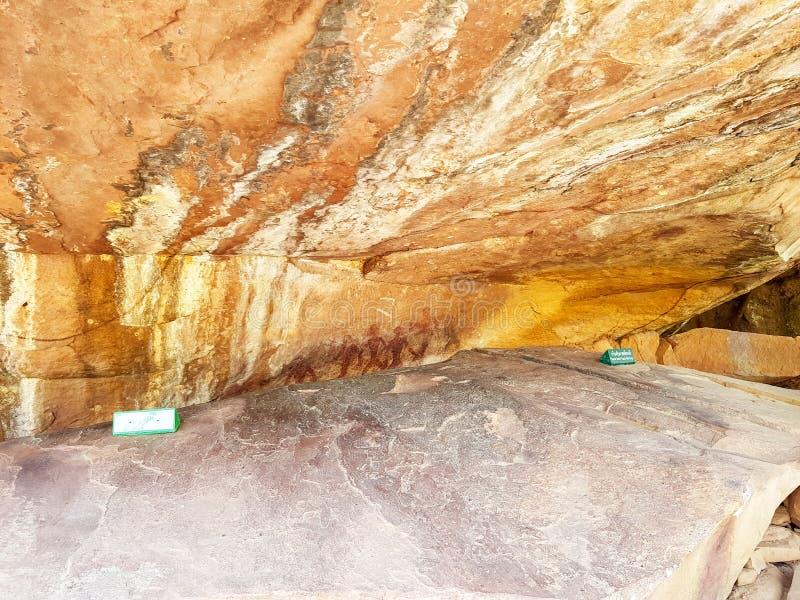 Pittura preistorica degli uomini nelle azioni su roccia dipinta con colore rosso dall'essere umano che vivono nell'area in mille  fotografia stock libera da diritti