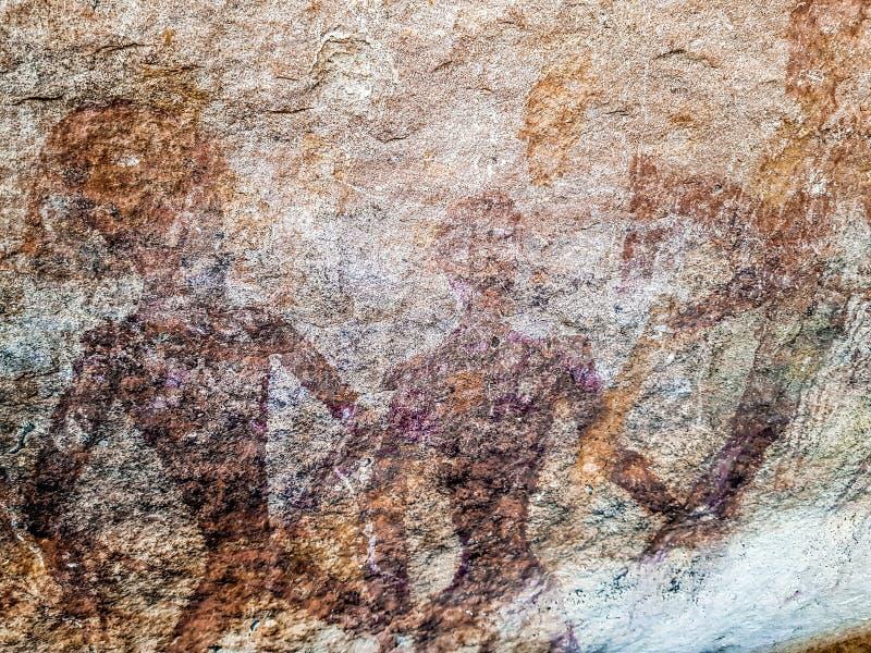 Pittura preistorica degli uomini nelle azioni su roccia dipinta con colore rosso dall'essere umano che vivono nell'area in mille  immagine stock libera da diritti