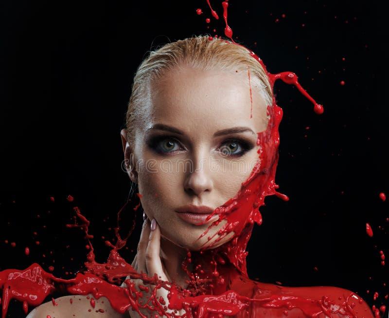 Pittura rossa che spruzza contro il fronte di una donna immagine stock libera da diritti
