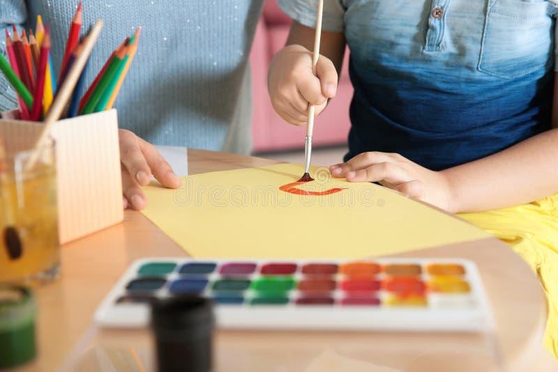 Pittura sveglia del bambino alla tavola con sua madre, primo piano Gioco della stanza immagini stock libere da diritti