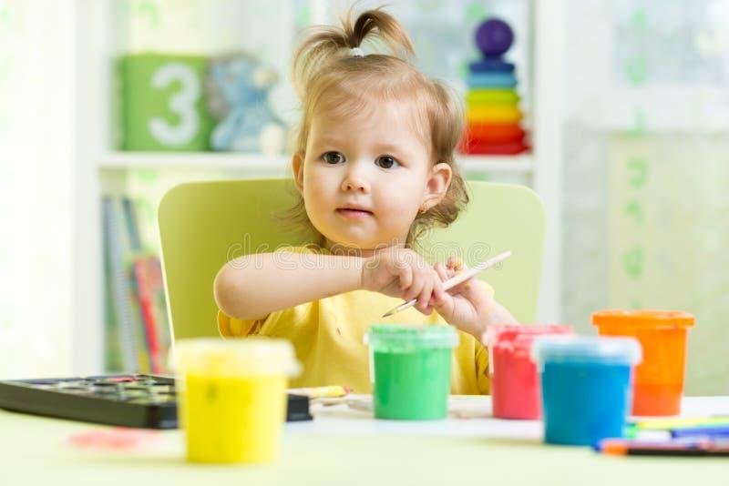 Pittura sveglia del piccolo bambino con il pennello e le pitture variopinte fotografie stock libere da diritti