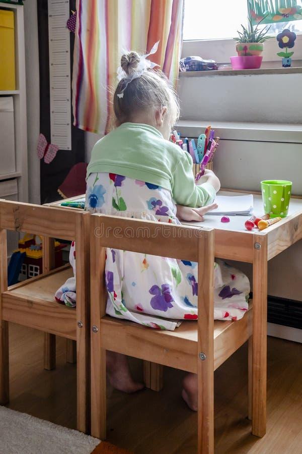 Pittura sveglia della bambina nella sua stanza a casa fotografie stock libere da diritti
