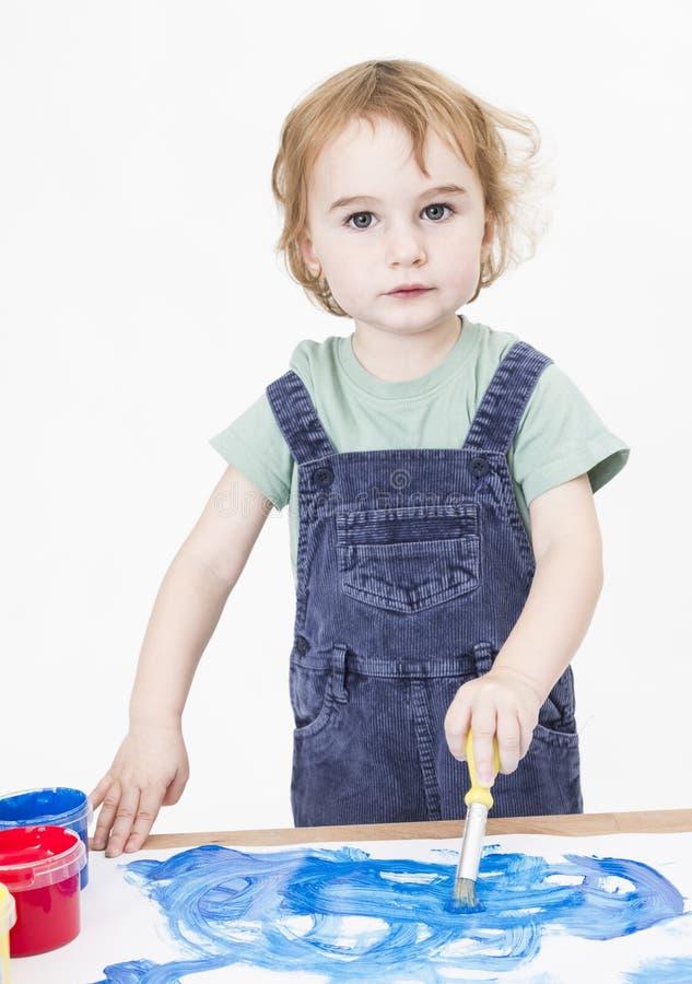 Pittura sveglia della ragazza sul piccolo scrittorio fotografia stock libera da diritti