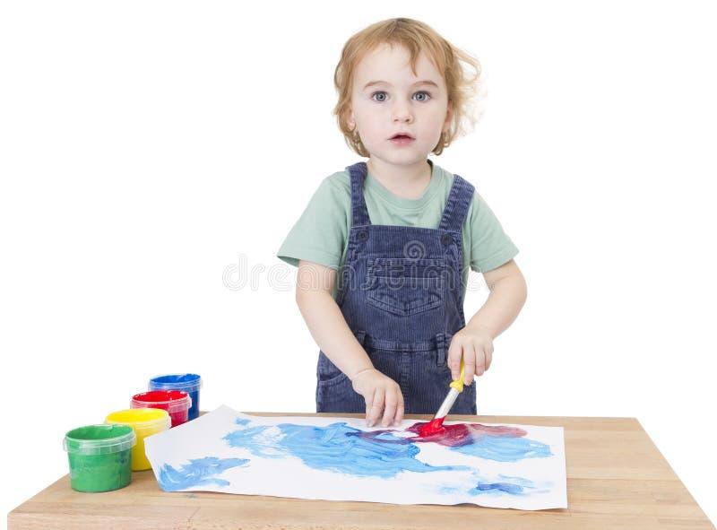 Pittura sveglia della ragazza sul piccolo scrittorio che guarda alla macchina fotografica immagine stock libera da diritti