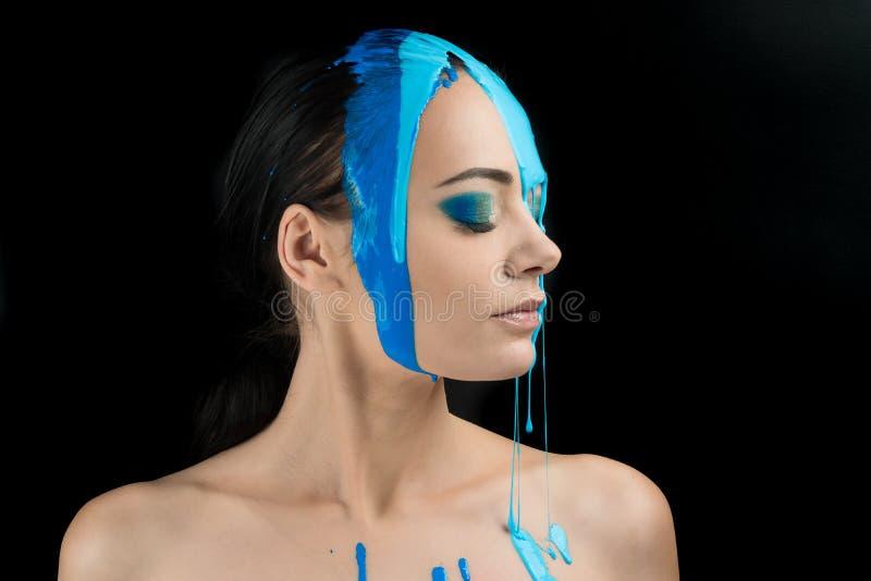 Pittura variopinta del fronte di Girl del modello di moda Ritratto di bella donna con la pittura di liquido corrente, trucco astr fotografia stock
