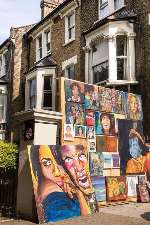 Pitture con i ritratti colorati della gente esibita sulla via fotografia stock