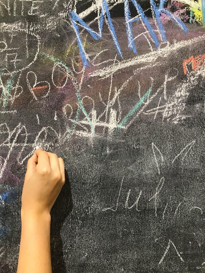 Pitture di un bambino da gesso su un consiglio scolastico fotografia stock libera da diritti