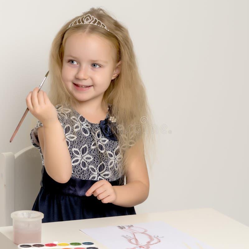 Pitture di una bambina con pittura e la spazzola immagine stock