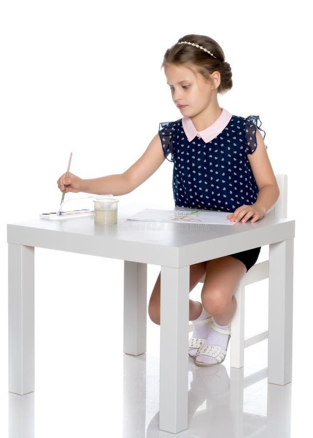Pitture di una bambina con pittura e la spazzola immagine stock libera da diritti