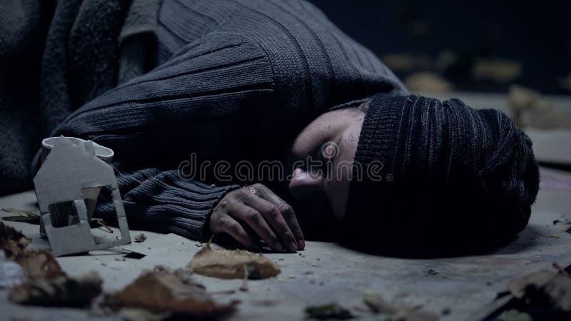 Pity sick refugee sleeping on street, paper house nearby, seeking asylum concept. Stock photo royalty free stock photo