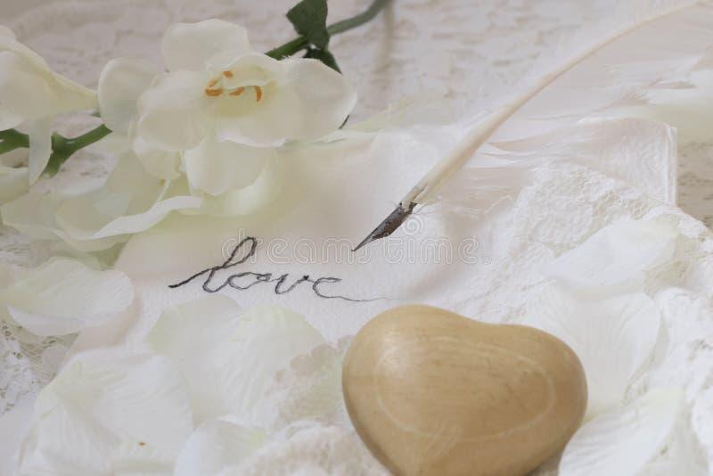 Piuma d'oca, lettera di amore, cuore di legno e fiori immagine stock