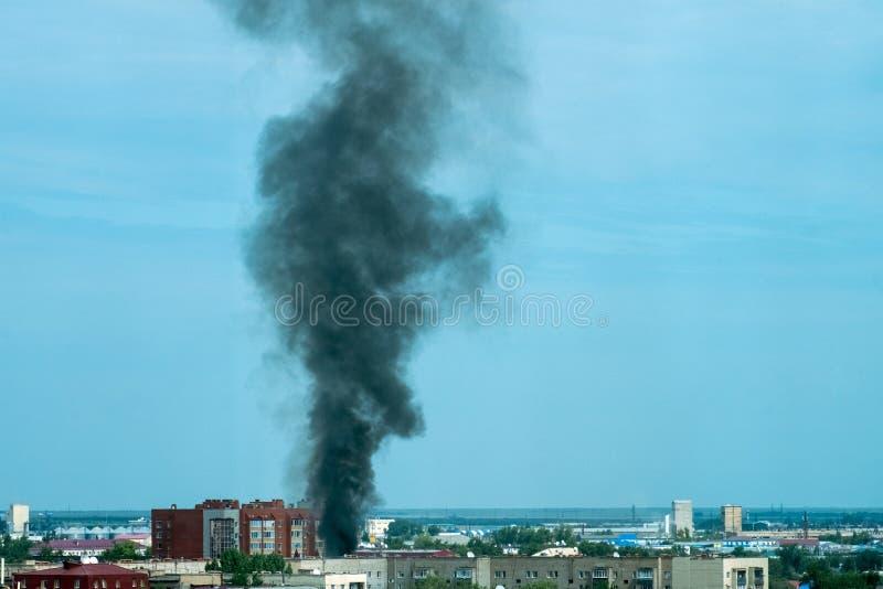 Piuma di fumo nero da un fuoco sopra la città al tramonto Incidente di Technogenic immagini stock libere da diritti