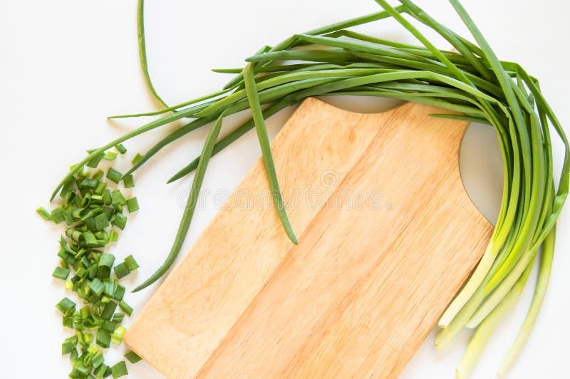 Piume di cipolla verde piatta e pezzi a fette su una tavola di legno isolata su fondo bianco, concetto di alimenti biologici, cop fotografia stock