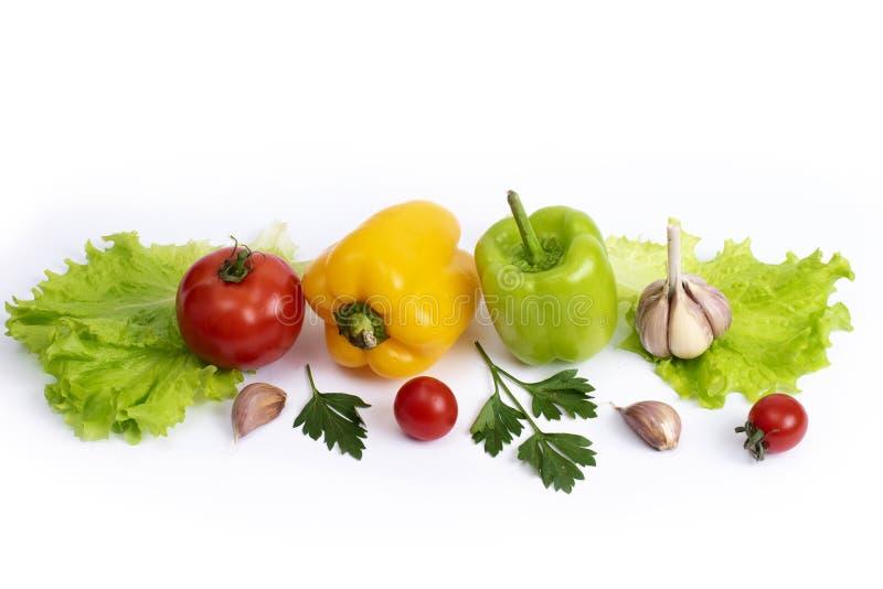 Piume gialle e verdi con i pomodori su un fondo bianco Pomodori ciliegia con i verdi e peperoni dolci su un fondo bianco immagine stock