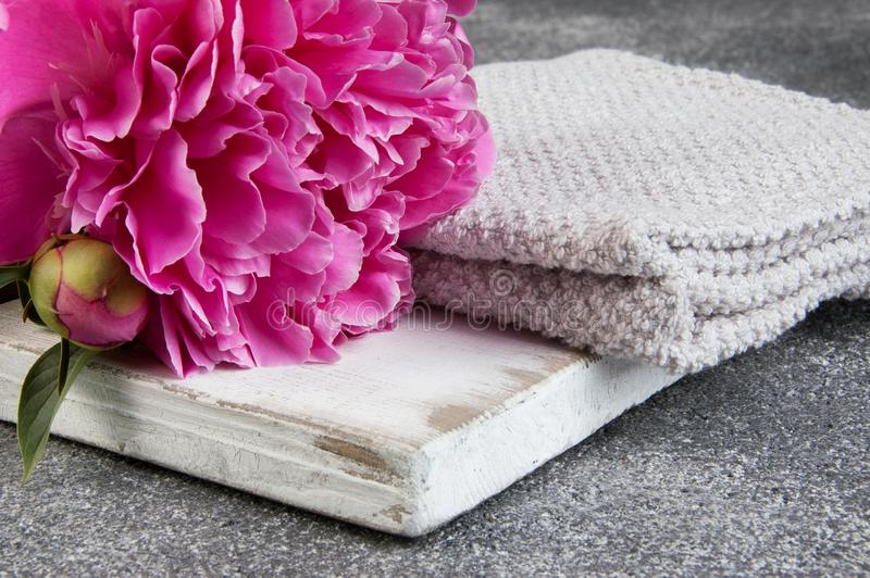 Pivoine rose, conseil blanc et serviettes sur le fond gris photographie stock libre de droits