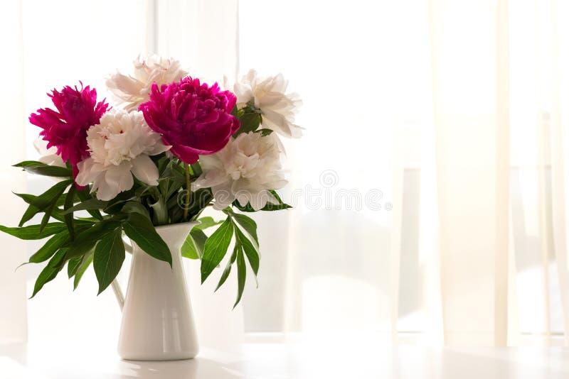 Pivoines blanches et roses dans le vase sur la table blanche image libre de droits