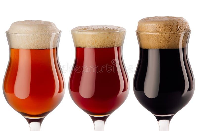 Piw wineglasses inkasowy nalewający wewnątrz zbliżenie z pianą odizolowywającą na białym tle - lager, czerwony ale, furtian - zdjęcie stock