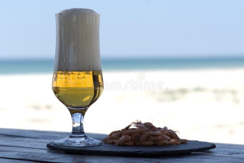 Piwny szkło i garnele na kamienia talerzu w cienia stole przeciw pogodnej plaży zamazywaliśmy tło obrazy royalty free