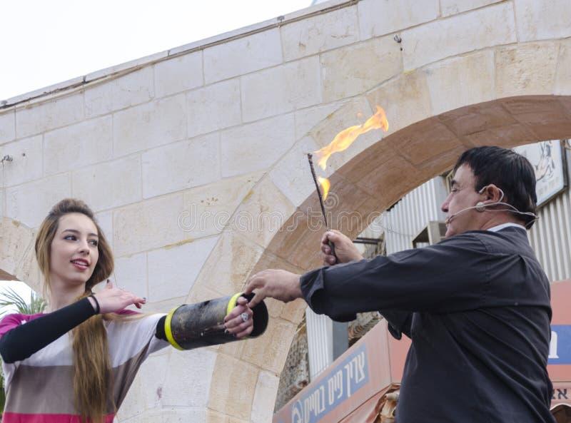piwo IZRAEL, Marzec, - 5, 2015: Fakir magik z pochodnią i kobieta asystentem - Purim zdjęcie stock