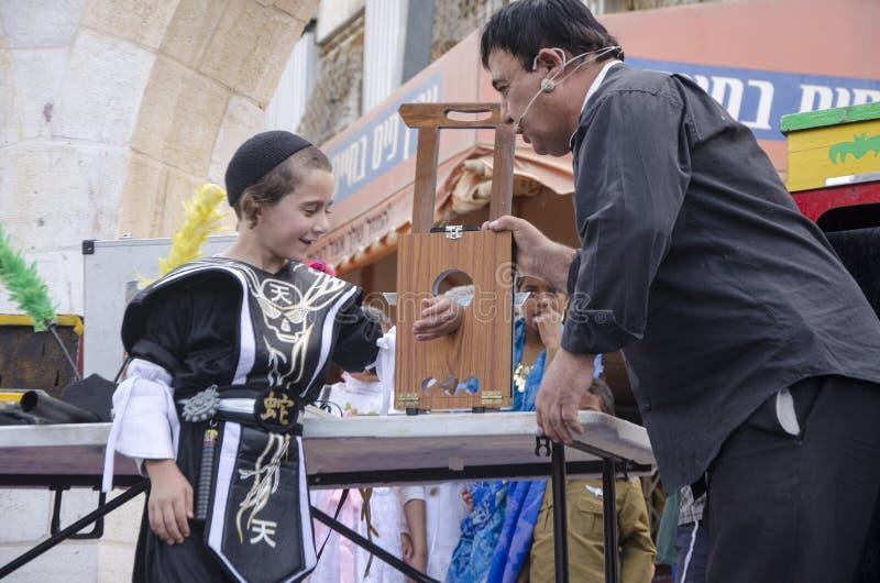 piwo IZRAEL, Marzec, - 5, 2015: Żydowska chłopiec w czarnym kostiumu i czerń wypiętrzamy na scenie z magikiem - Purim zdjęcia stock