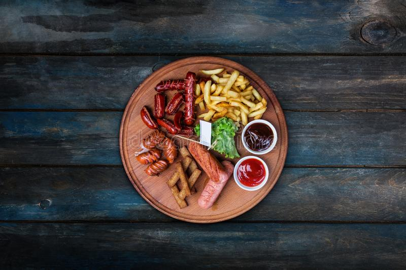 Piwo przekąski ustawiać Piec na grillu francuzów dłoniaki i kiełbasy słuzyć z pomidorem i BBQ kumberlandem zdjęcie stock