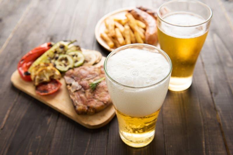 Piwo w szkle z wyśmienitym stkiem i francuzem smaży na drewnianym plecy zdjęcie royalty free