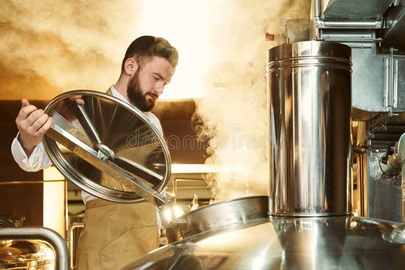 Piwowar patrzeje w kruszcowym parzenie czajniku z kontrparą zdjęcie stock
