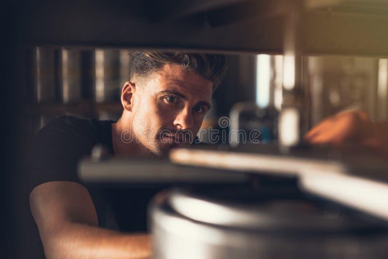 Piwowar pracuje na piwnej linii produkcyjnej przy browarem fotografia stock