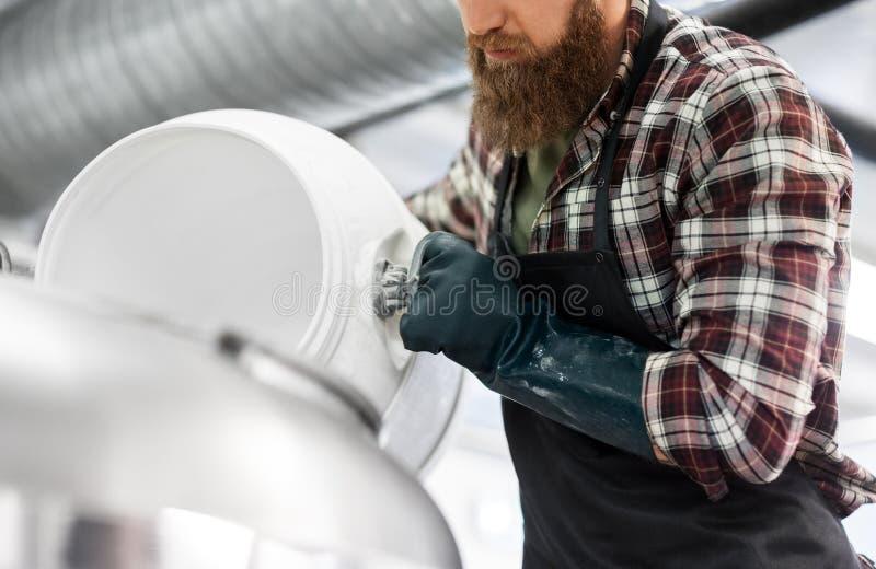 Piwowar pracuje przy rzemiosło browarem lub piwną rośliną zdjęcie stock