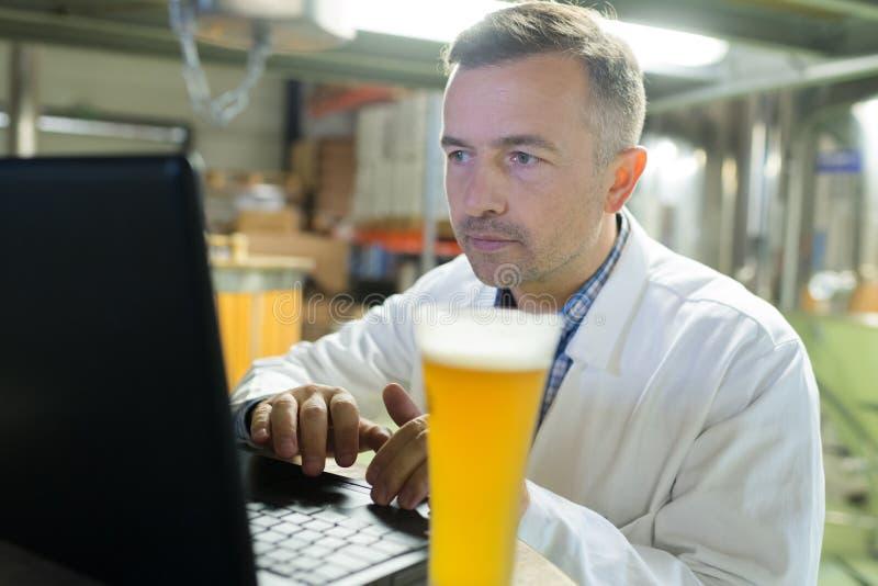 Piwowar pracuje z laptopem przy produkcją obraz royalty free
