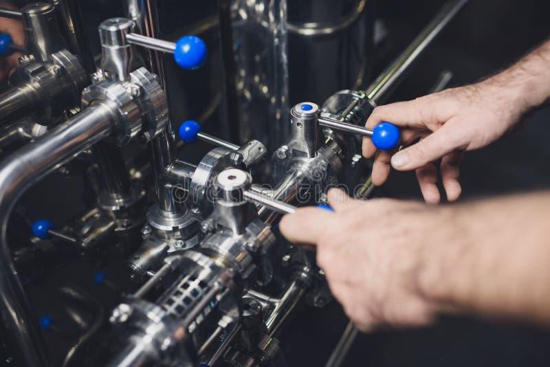 Piwowar pracuje z przemysłowym wyposażeniem obrazy stock