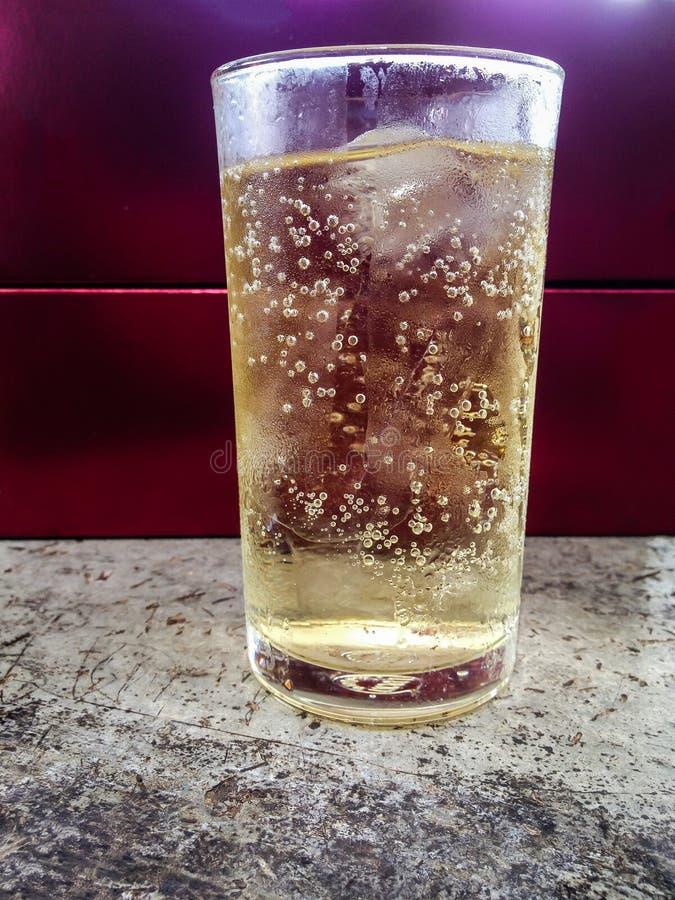 Piwowar przygotowywa pić w szkle soda na czerwonym tle zdjęcia royalty free